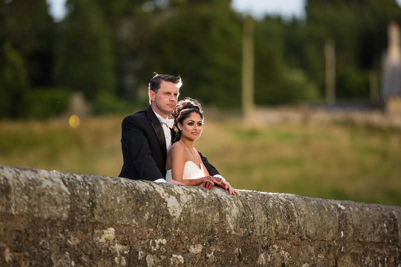 Bride and groom leaning on wall