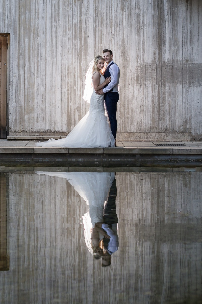Bride and groom with reflection in water