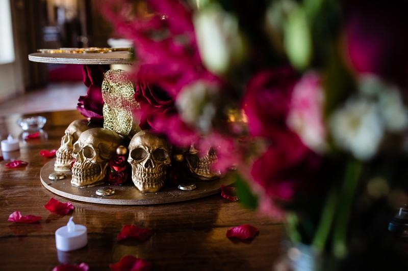 Gold skulls at base of wedding cake