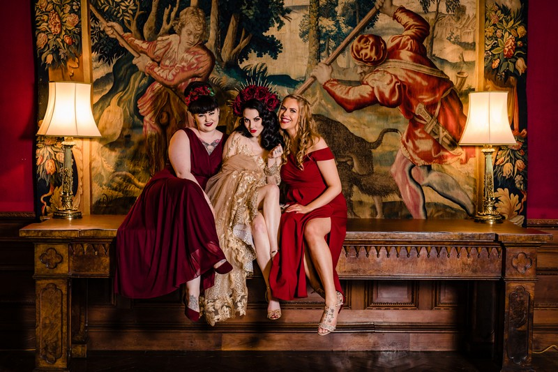 Bride and bridesmaids sitting in front of old tapestry at Thornton Manor