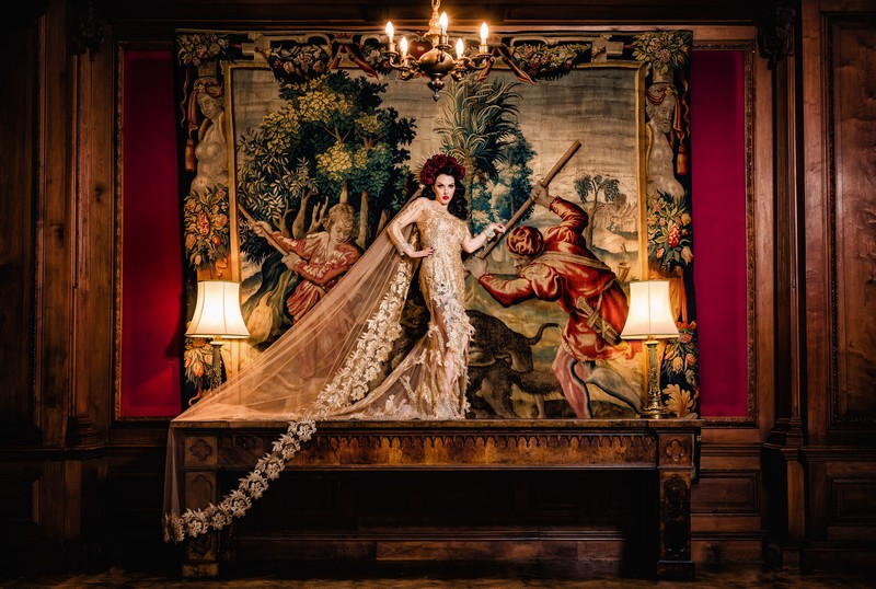 Bride standing on table in front of old tapestry at Thornton Manor