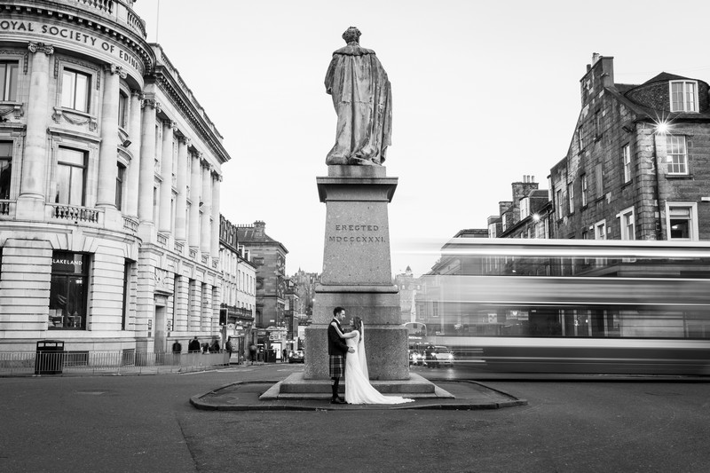 Couple posing my monument in middle of road
