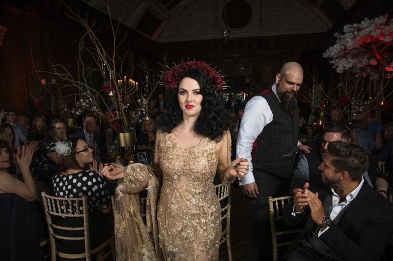 Gothic bride and groom walking to dance floor