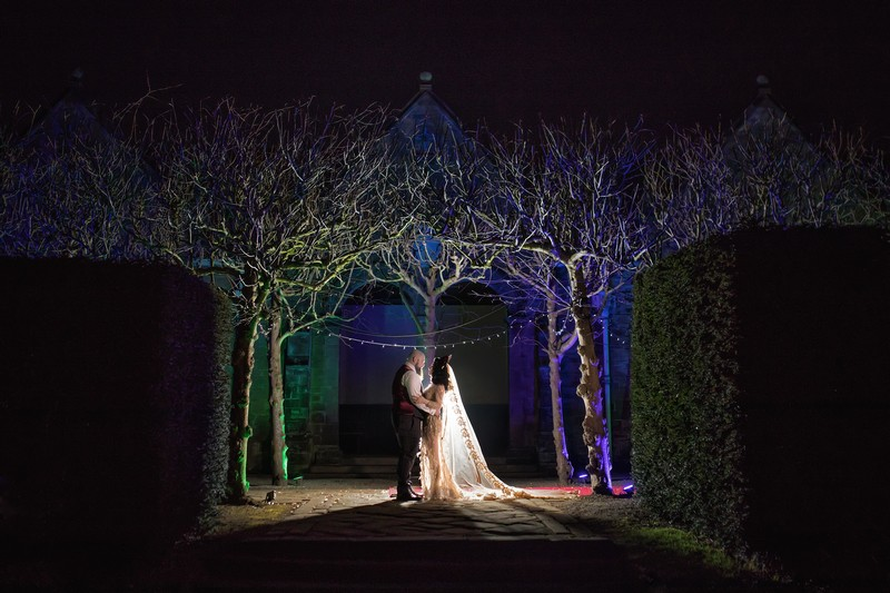 Bride and groom under trees at Thornton Manor at night