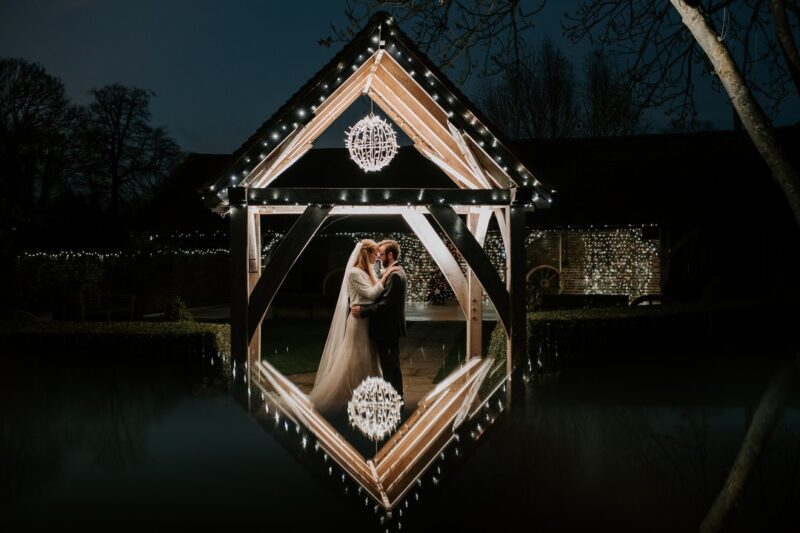 Bride and groom touching heads below canopy with reflection below - Picture by Michelle Cordner Photography