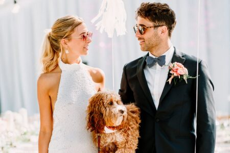 Bride and groom wearing sunglasses and holding a dog - Picture by Jessy Papasavva Photography