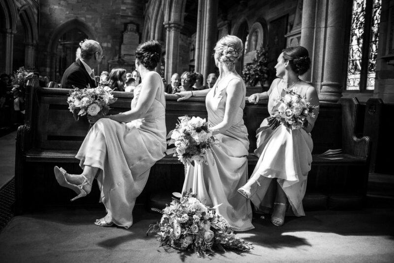 Three bridesmaids sitting in church looking over their shoulders at the same time - Picture by Nick Brightman Photography