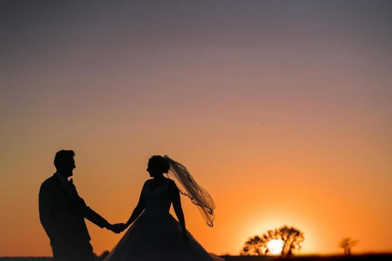 Silhouette of bride and groom against orange sky as sun sets - Picture by Nick Church Photography