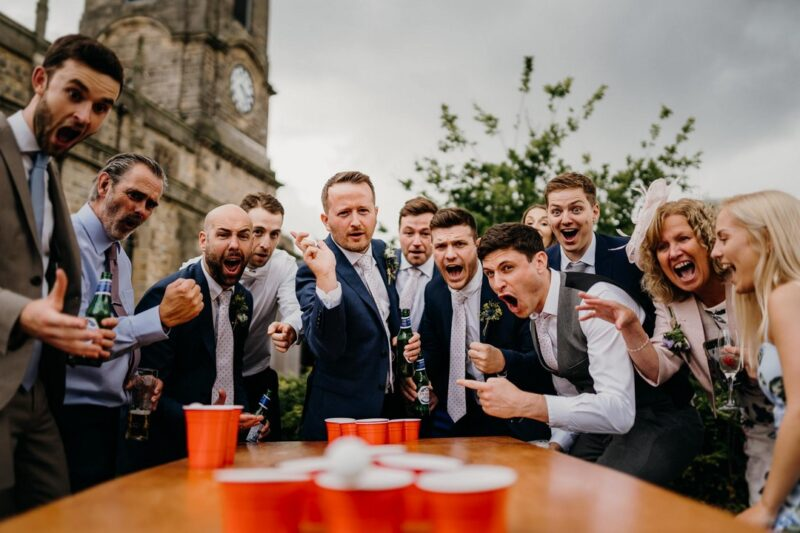 Man playing beer pong at wedding watched by excited guests - Picture by Sawyer and Sawyer Photography