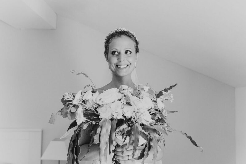Happy bride smiling as she holds bouquet - Picture by The Sweet Days