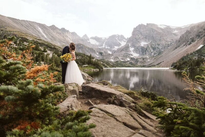 Bride and groom standing by lake with mountains in background - Picture by Larsen Photo Co.