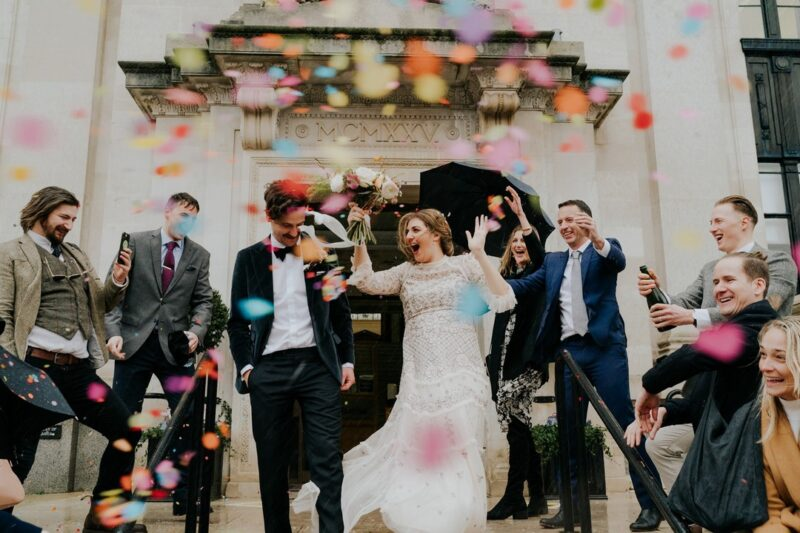 Bride and groom walking through colourful confetti shower - Picture by Joasis Photography