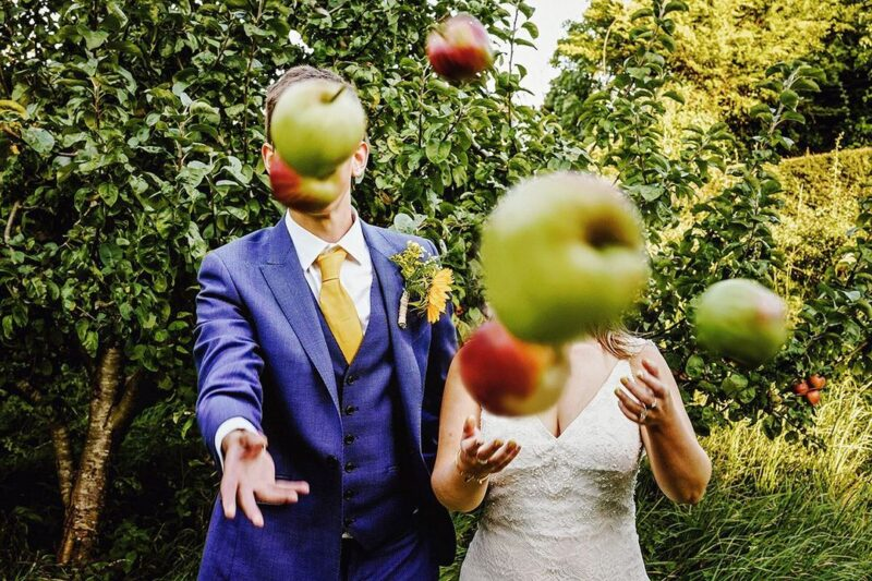 Bride and groom throwing apples at camera - Picture by Steven Rooney Photography