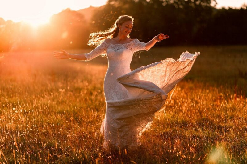 Bride twirling in field in hazy sunshine - Picture by Rich Howman