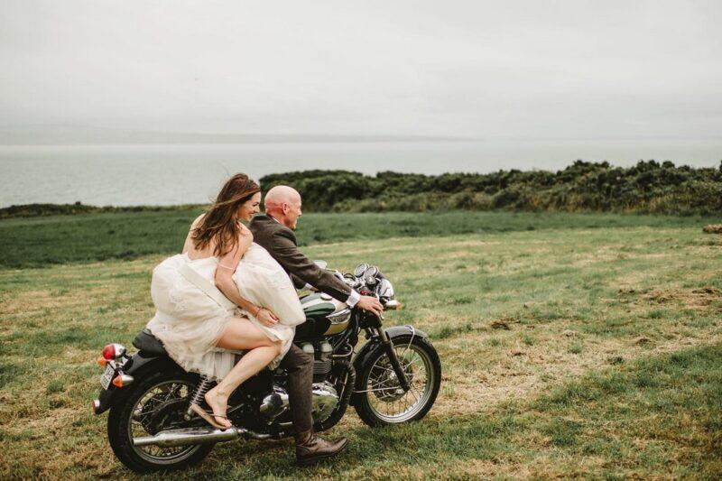 Bride and groom riding across field on motorbike - Darek Novak Photography