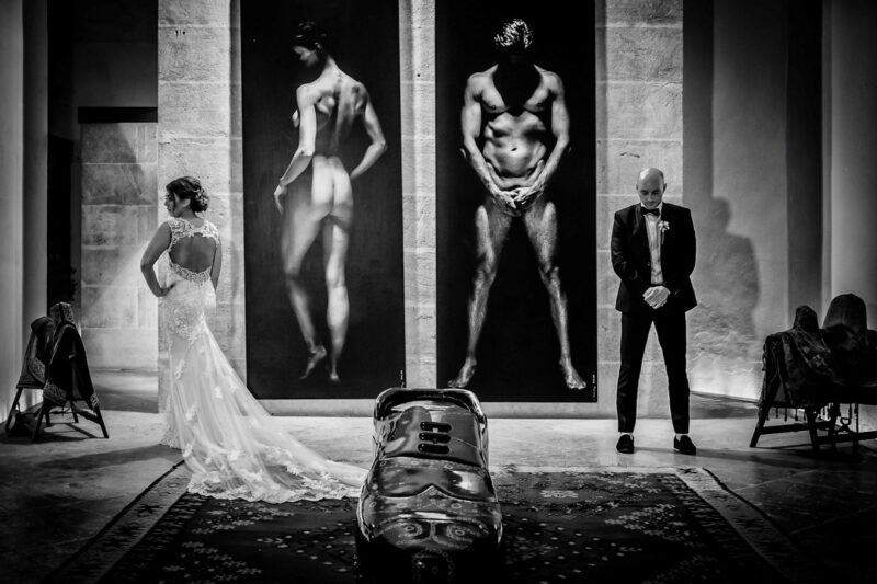 Bride and groom copying poses from pictures behind them - Picture by Graham Warrellow Photography