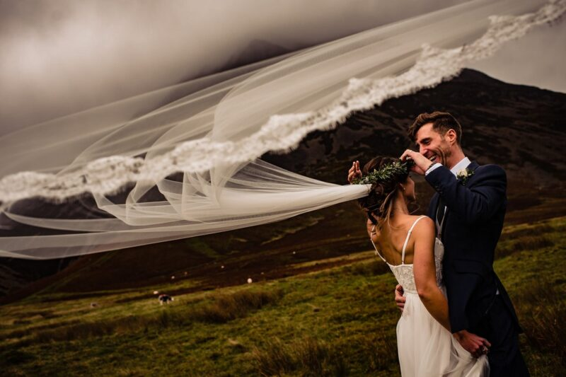 Groom adjusting bride's flower crown as veil blows in the wind - Picture by Ricky Baillie Photography