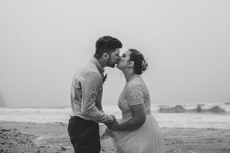 Bride and groom kissing in front of the sea - Picture by Tracey Warbey Photography
