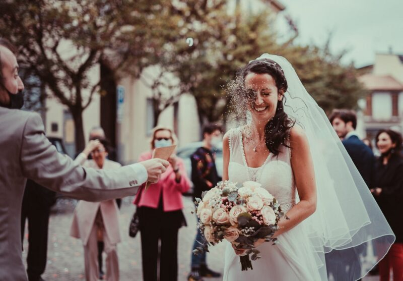 Bride being hit in the face by confetti - Picture by Anna Pierobon Photography