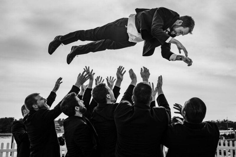 Groomsmen throwing groom in the air - Picture by Chad Winstead Photography