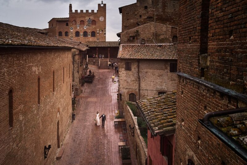 Bride and groom walking down street in Tuscany - Picture by D2 Photography