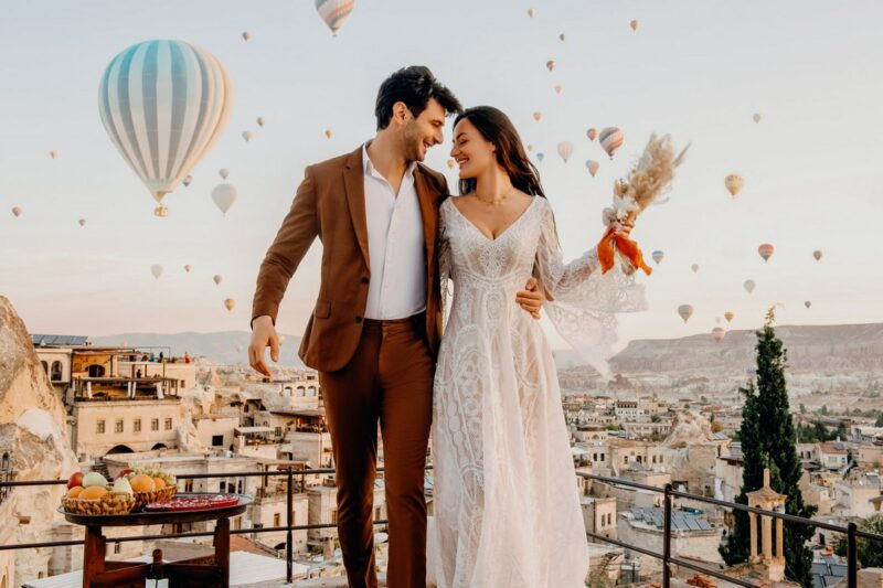 Bride and groom standing on balcony with hot air balloons in sky behind them - Picture by Emma-Jane Photography