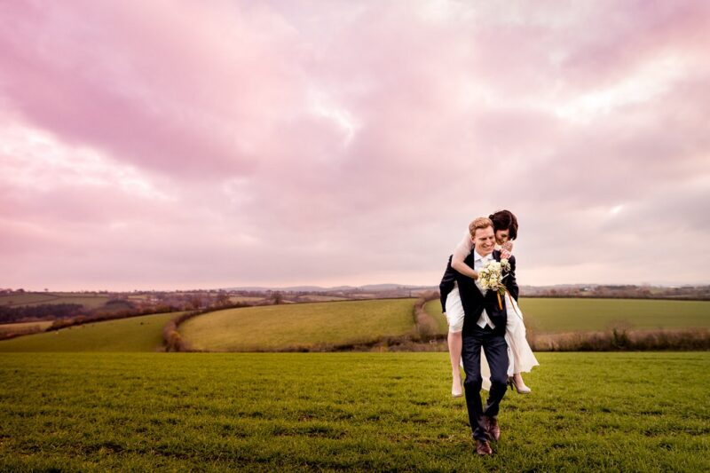 Groom giving bride piggy back ride across field with pink sky overhead - Picture by Lee Maxwell Photography