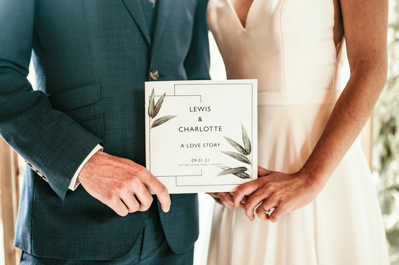 Bride and groom holding Love Story booklet by CherryTop Weddings