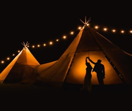 Picture from outside a tipi at night showing silhouette of bride and groom dancing inside - Picture by Robin Goodlad Photography