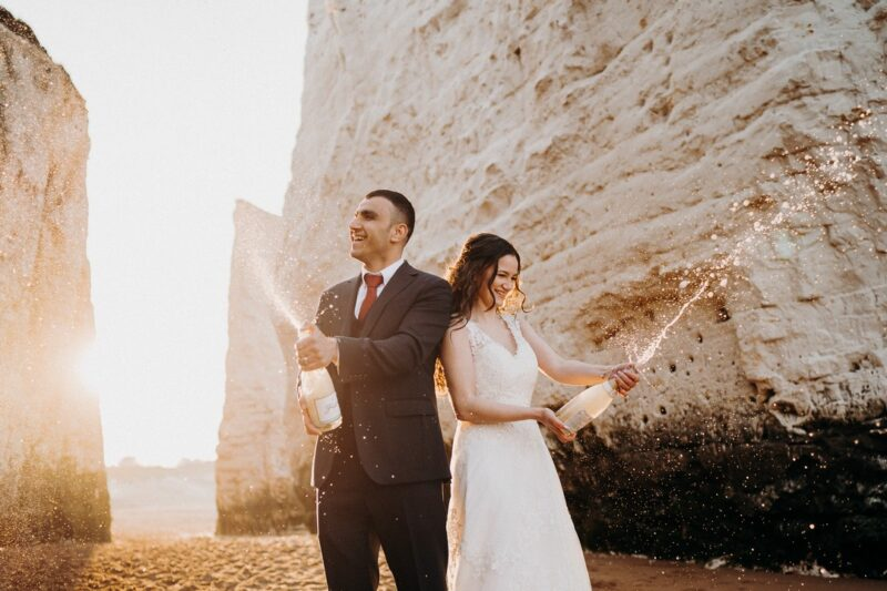 Bride and groom spraying Champagne on beach - Picture by Voyteck Photography