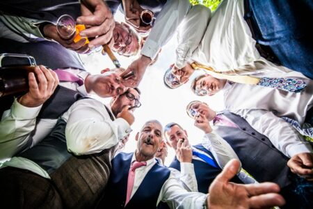 Groomsmen in circle looking down at camera and smoking cigars - Picture by Peter Rollings Photography