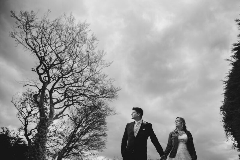 Bride and groom holding hands between trees - Picture by IG Time Photography