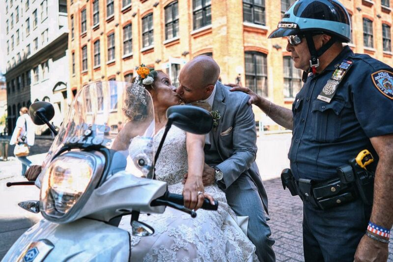 Bride and groom kissing on police officer's scooter as her taps groom on the shoulder - Picture by Emin Kuliyev