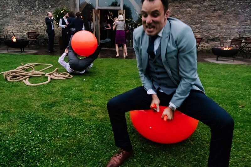 Two men bouncing on Space Hoppers at wedding - Picture by Kristian Leven Photography