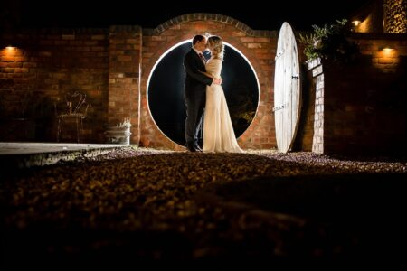 Bride and groom kissing in front of circular hole in wall at night - Picture by Damian Burcher