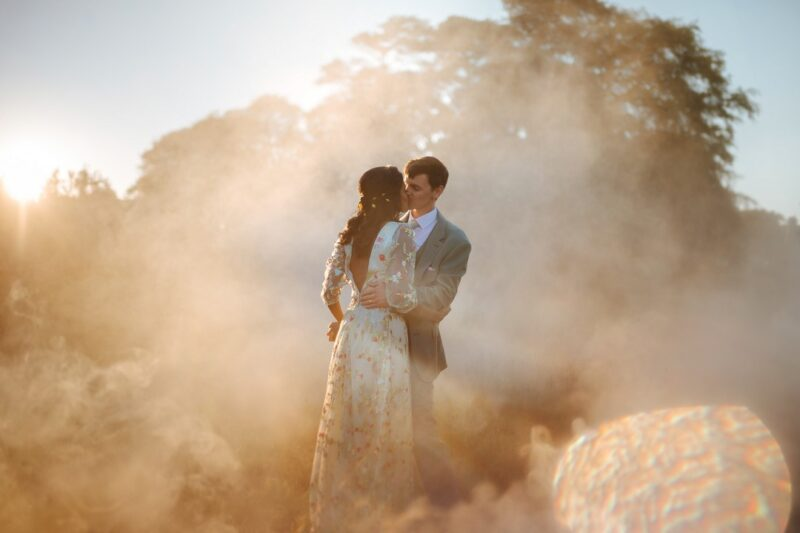 Bride and groom kissing in hazy sunshine surrounded by smoke - Picture by Joab Smith