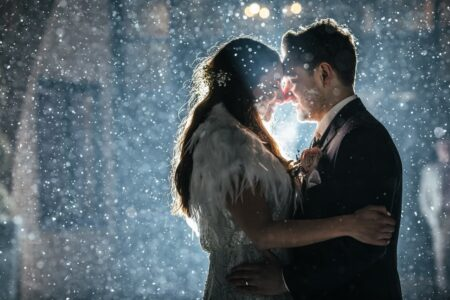 Bride and groom facing each other in rain at night - Picture by Rafe Abrook Photography