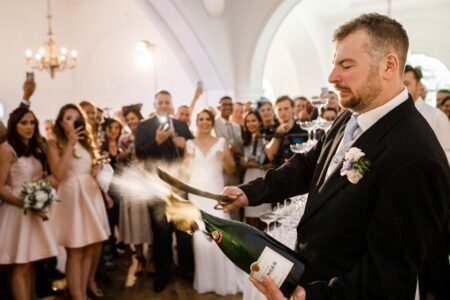 Man at wedding opening champagne bottle with sword - Picture by Damion Mower Photography