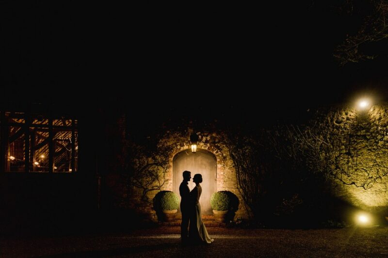 Bride and groom lit up as they stand in doorway of wedding venue at night - Picture by Murray Clarke