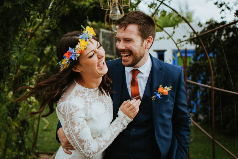 Bride with colourful flower crown laughing with groom - Picture by Alexa Poppe Wedding Photography