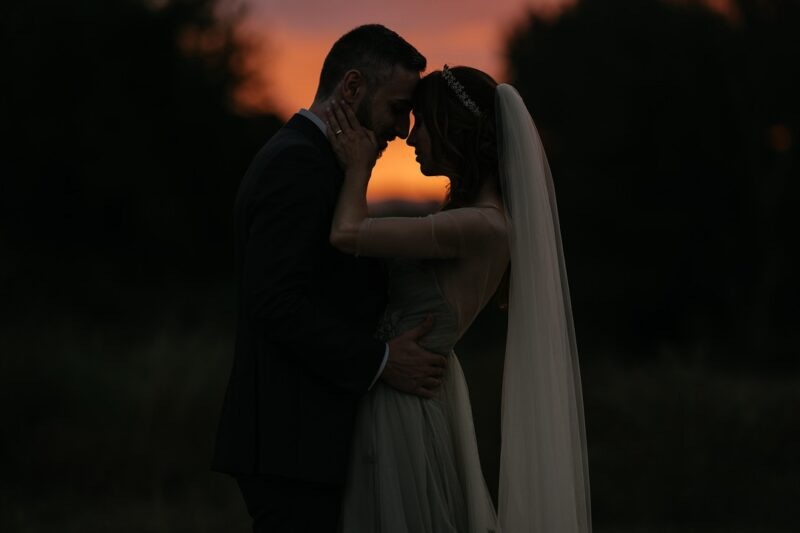 Bride and groom touching heads in dusk light - Picture by IstantiSenzaTempo