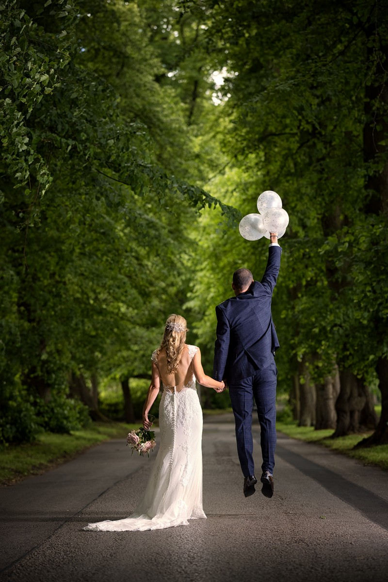 Bride holding groom's hand as he is pulled into the air by balloons - Picture by Paul Baybut Photography