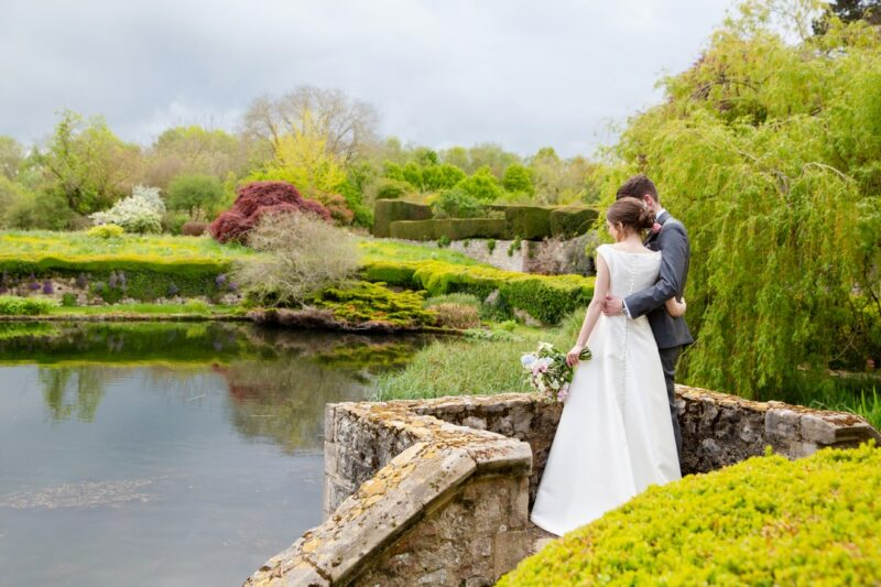 Bride and groom standing by lake at wedding venue - Picture by Helen England Photography