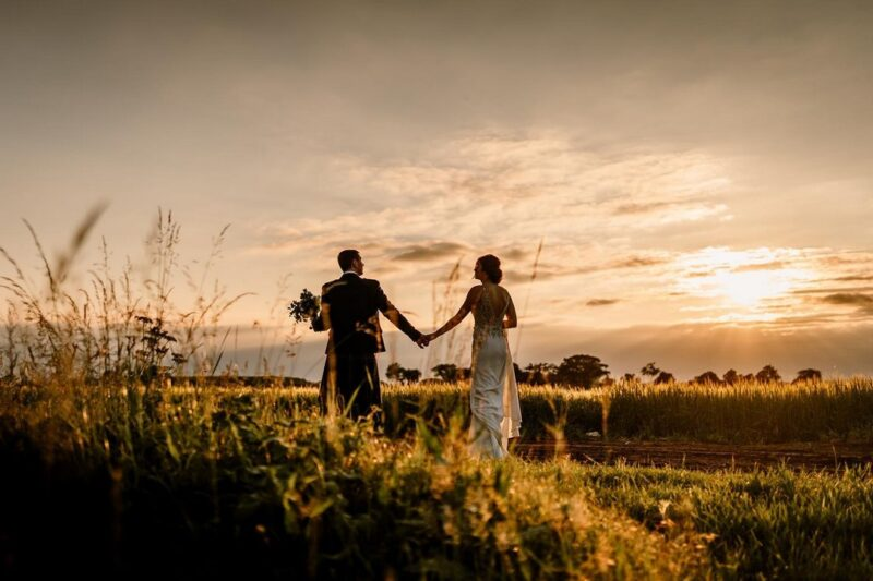Bride and groom walking holding hands as sun sets - Picture by Hayley Baxter Photography