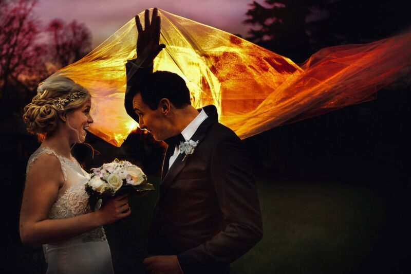 Sun shining through bride's veil as groom holds it up in the air - Picture by Kevin Belson Photography