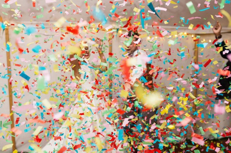 Bride and groom dancing behind colourful confetti - Picture by Paul Joseph Photography