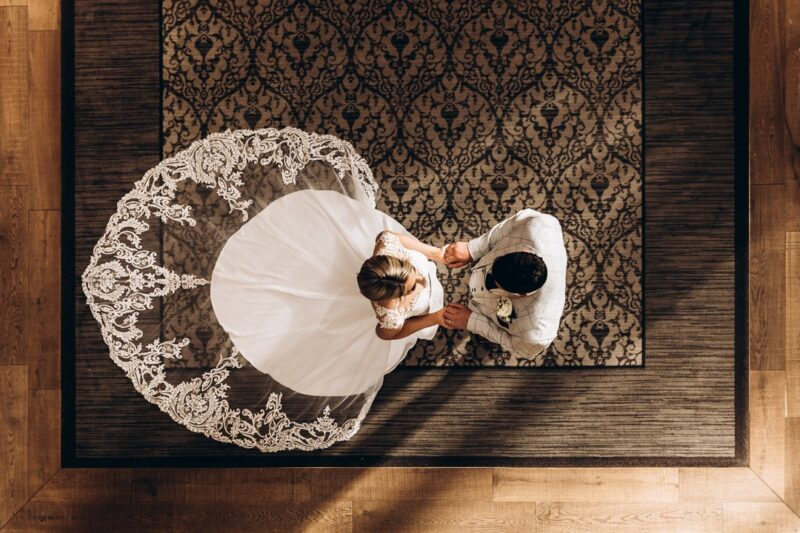 Aerial shot of bride facing groom with her elaborate dress train behind her - Picture by Angela Waites Photography