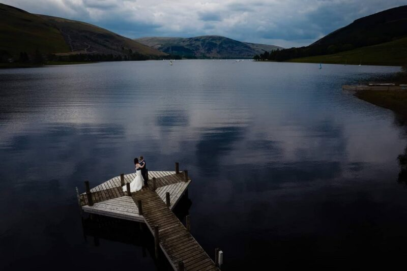 Bride and groom standing on jetty over loch in Scotland - Picture by Andy Dane Photography