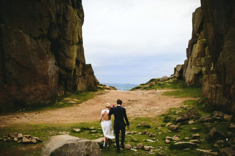 Bride and groom walking between two cliffs - Picture by Craig Williams Photography