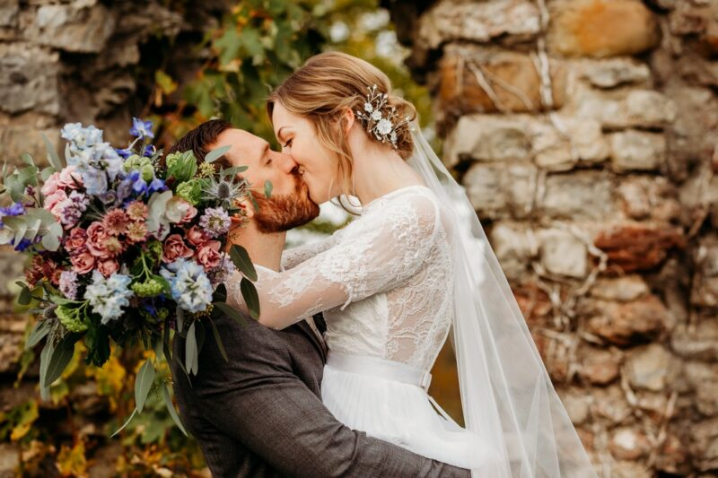 Bride holding bouquet kissing groom - Picture by When Charlie Met Hannah